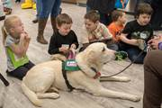 Students read to dogs at the Read Across America Day event